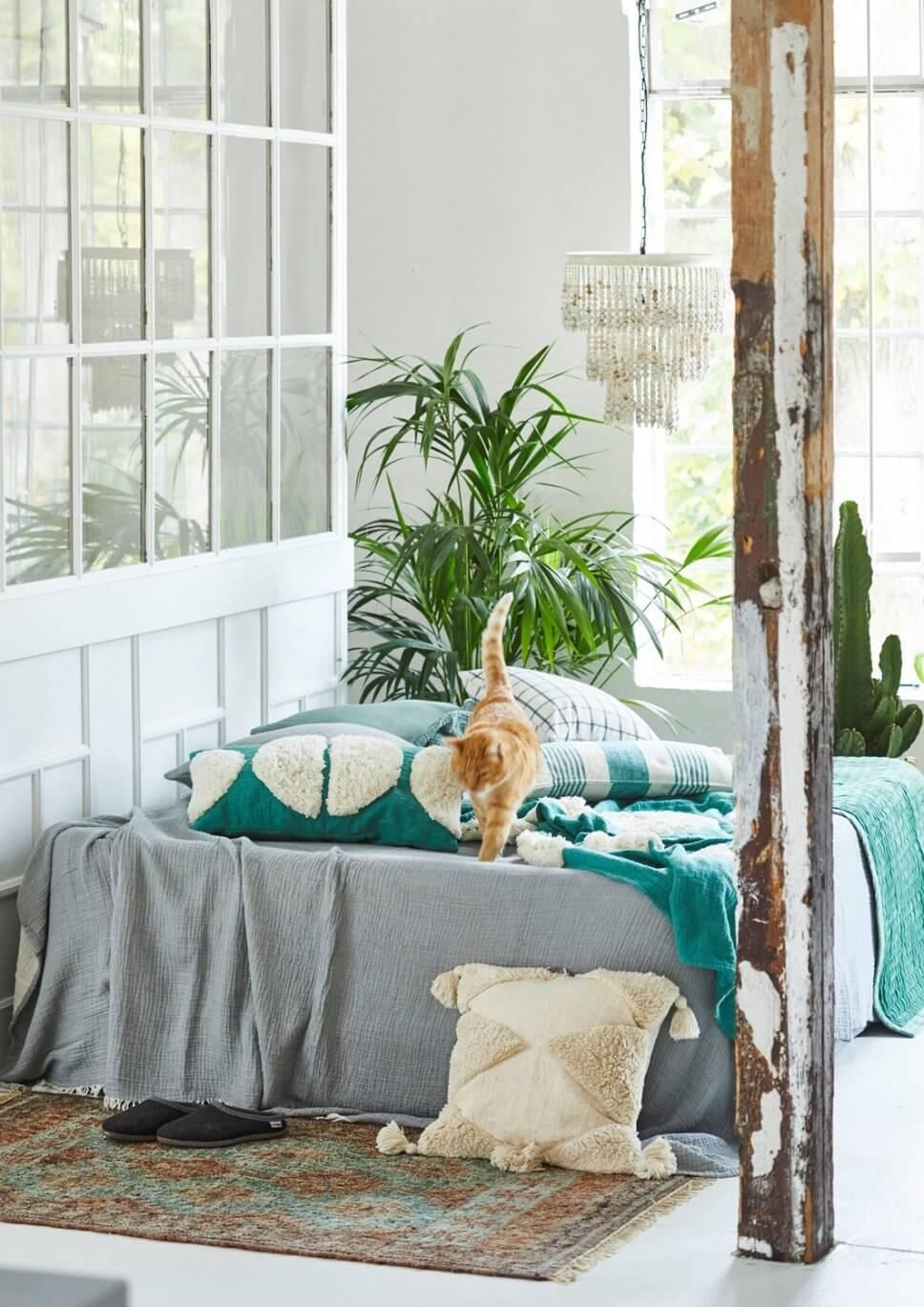 Schlafzimmer mit vielen Kissen und Decken auf dem Bett