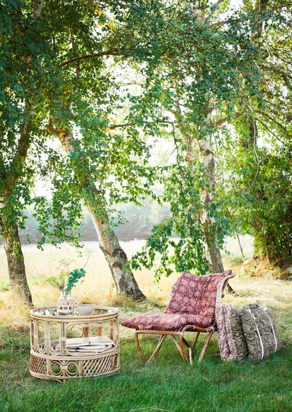 Bambusmöbel stehen unter großen Baum