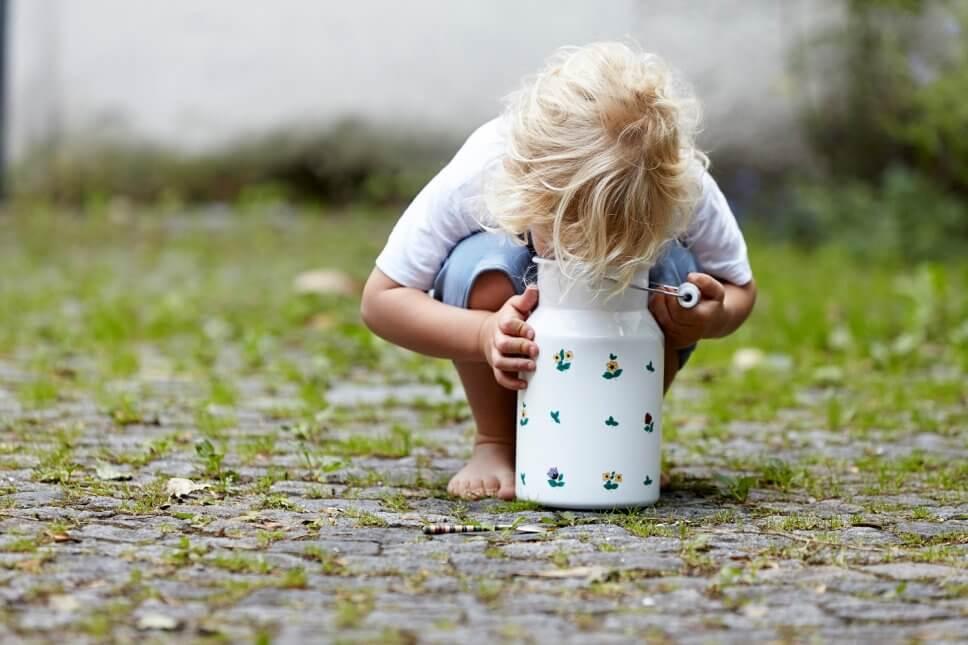 Blonder Junge schaut auf Kopfsteinpflaster im Milchkanne