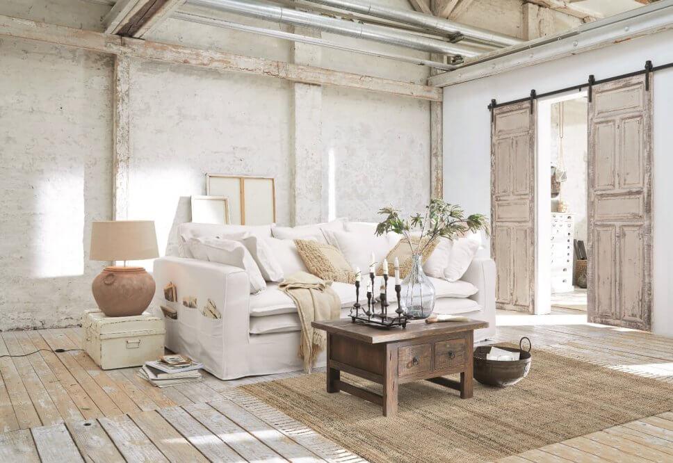 Weißes Hussensofa im Landhaus mit alten Holzschiebetüren