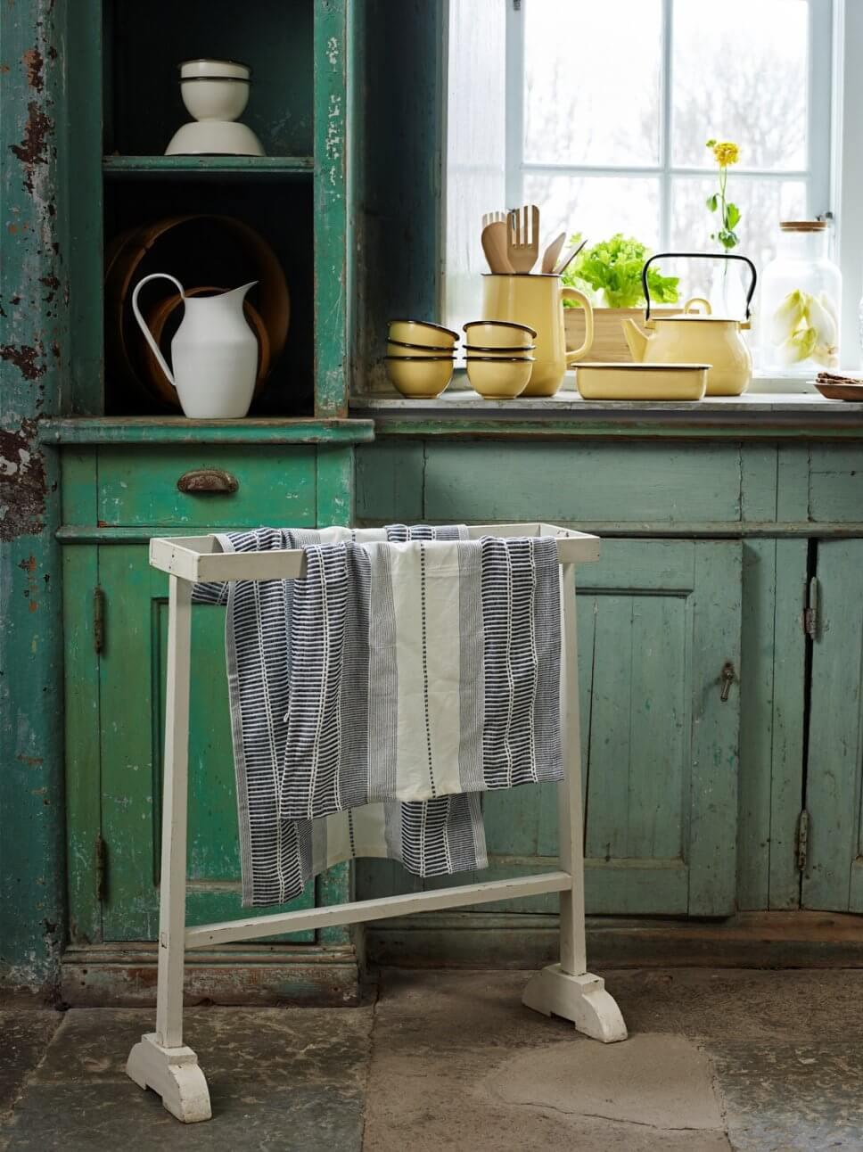 Grüne Landhausküche mit verschiedenen Geschirrtüchern