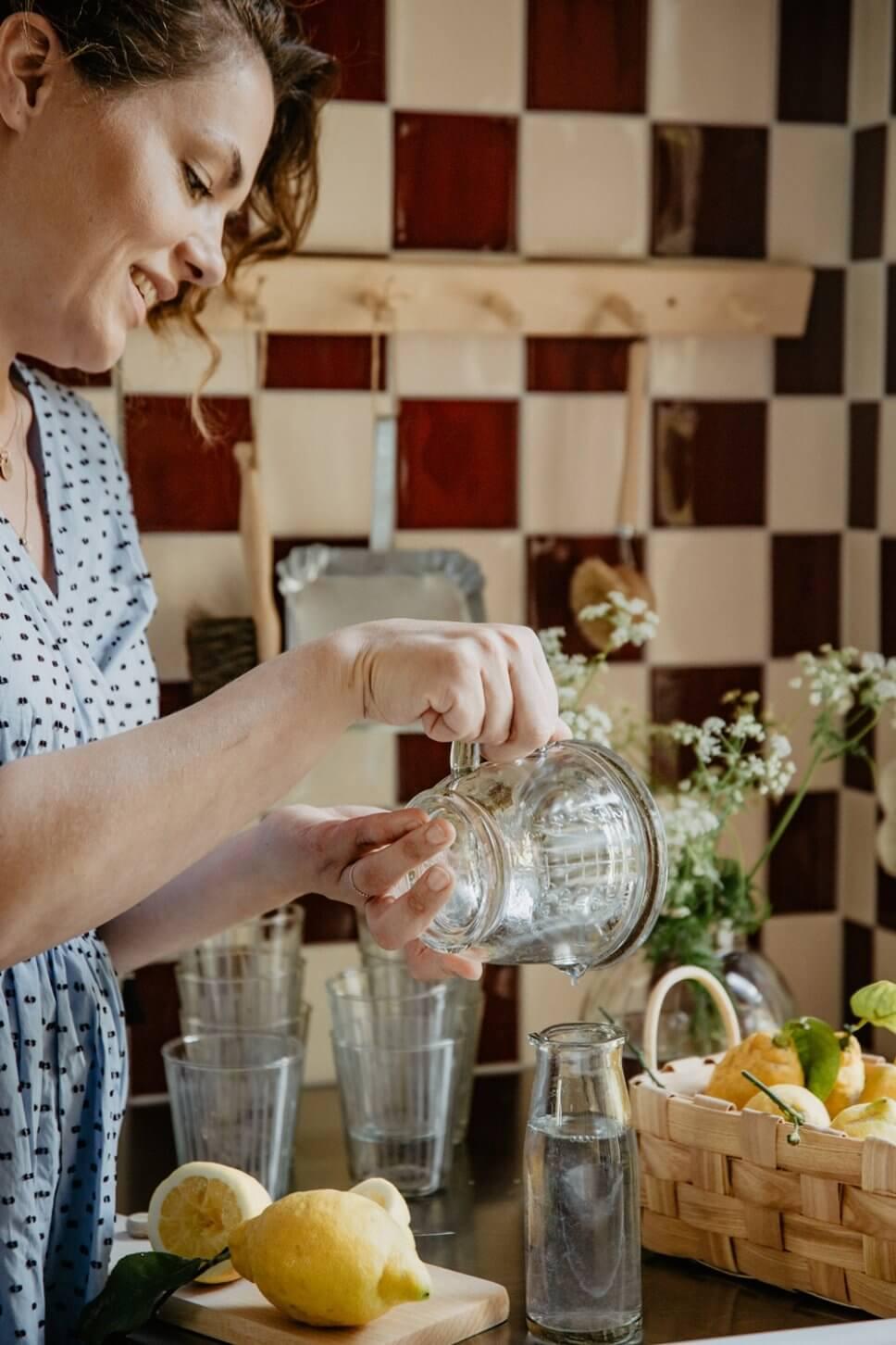 Frau macht Limonade in Landhausküche