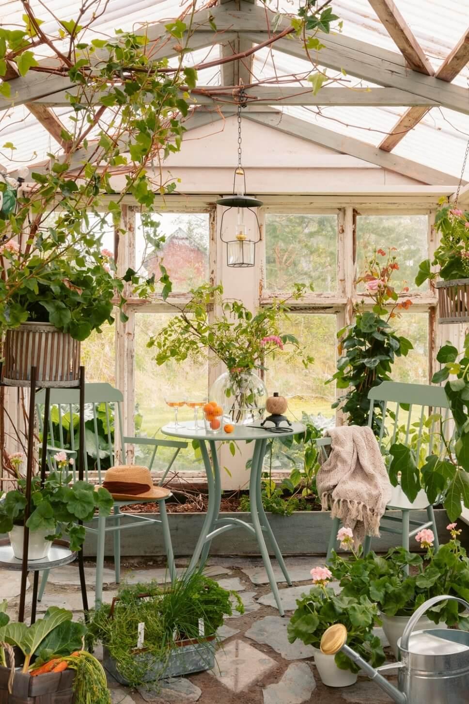 Hellgrüne Stühle um einen Bistrotisch in einem üppig bepflanzten Wintergarten