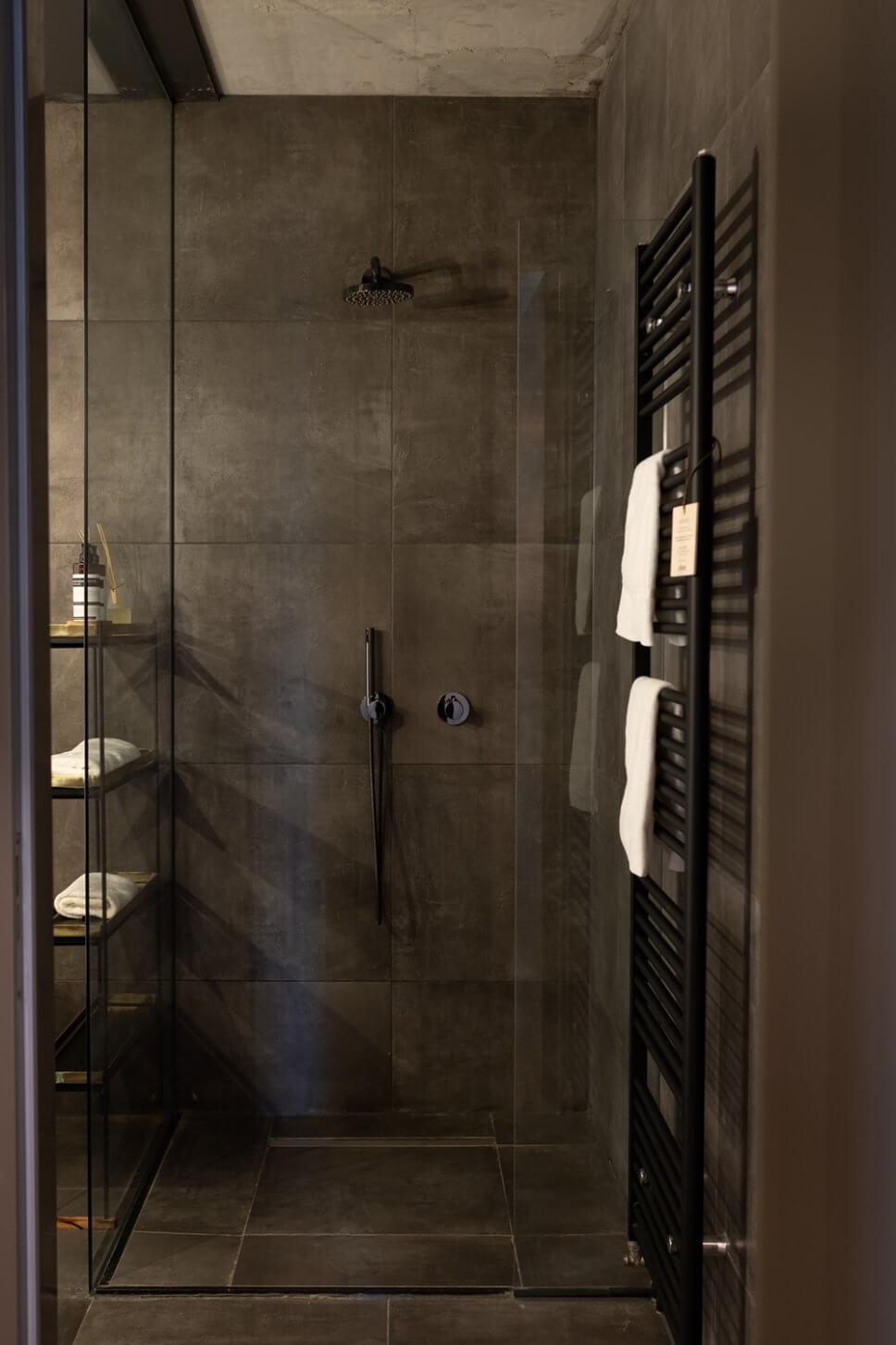 Dunkel geflieste begehbare Dusche