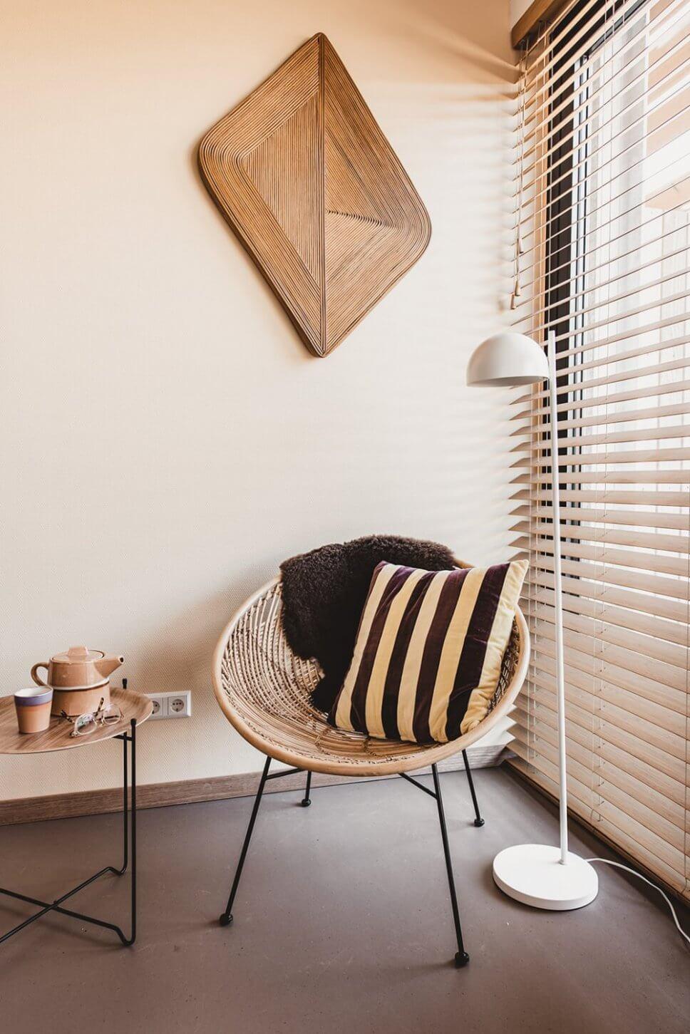 Modern eingerichteter Wohnraum mit Korbsessel, auf dem ein gestreiftes Kissen und ein Schaffell liegen
