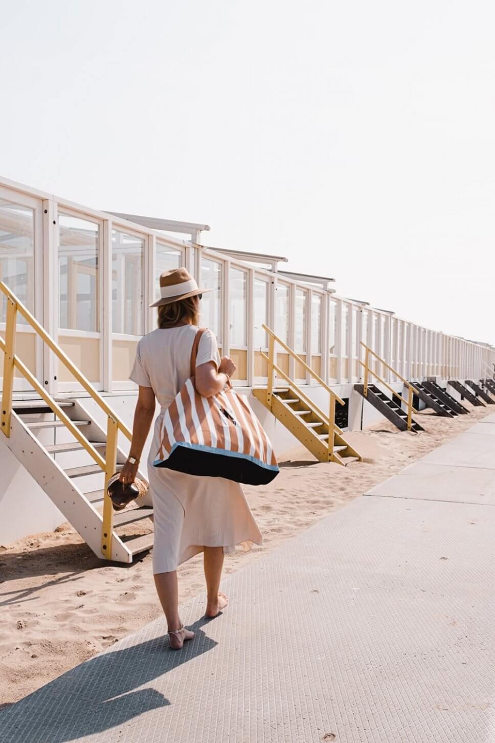 Frau mit einer Strandtasche über der Schulter geht an einer Reihe Badehäuser vorbei