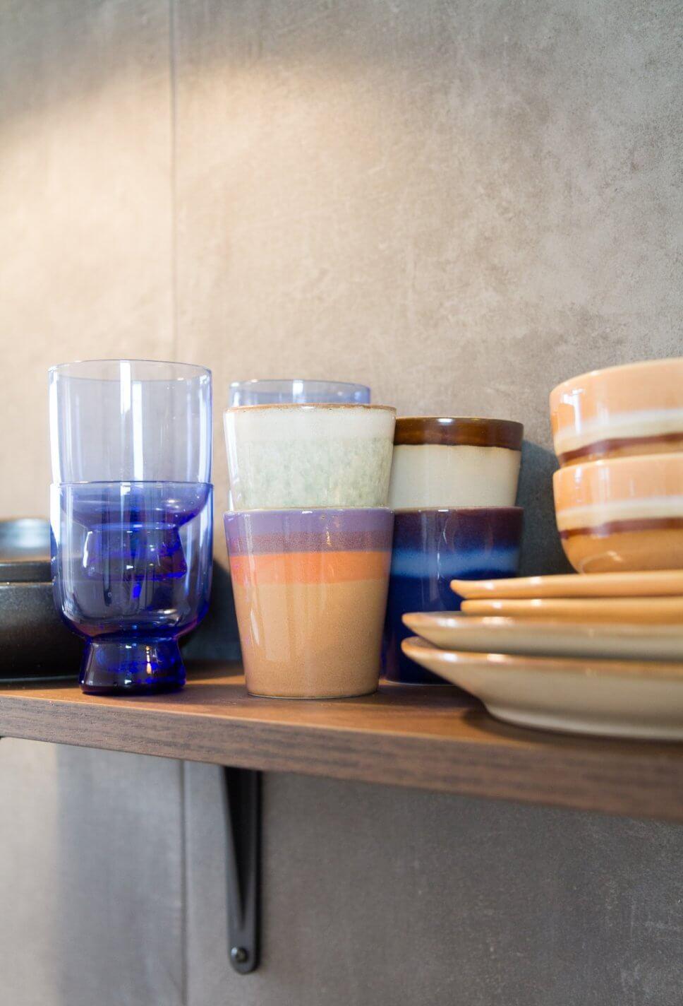 Keramikbecher, Teller und Gläser stehen auf Regalbord