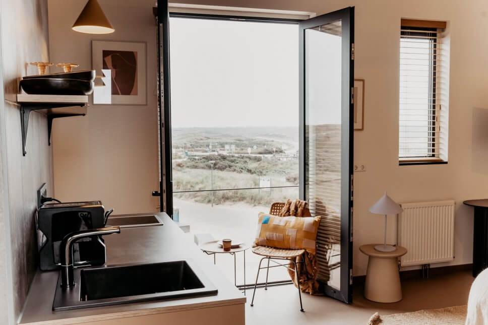 Modern eingerichteter Wohnraum mit Küchenzeile im Vordergrund