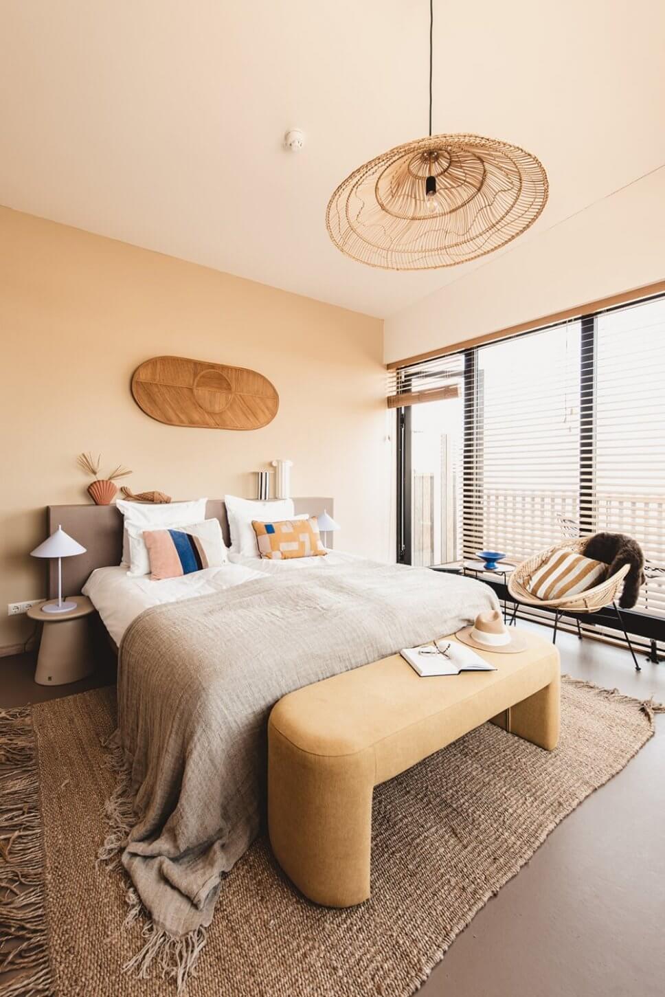 Modern eingerichtetes Schlafzimmer mit vielen Kissen im Bett