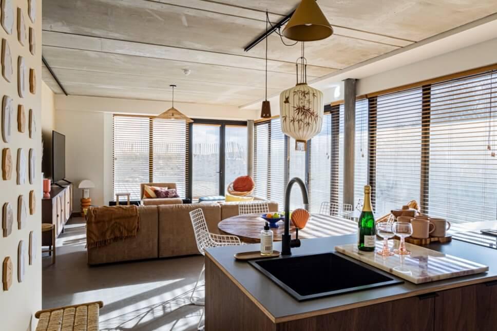 Modern eingerichteter Wohnraum mit Kücheninsel im Vordergrund