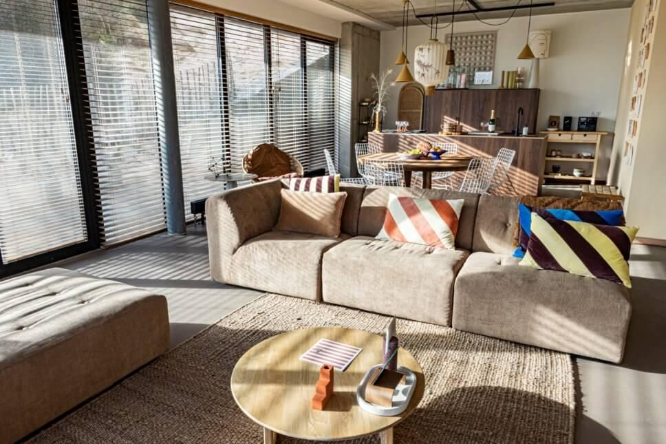 Modern eingerichteter Wohnraum mit Sofa und Essplatz sowie offener Küche im Hintergrund