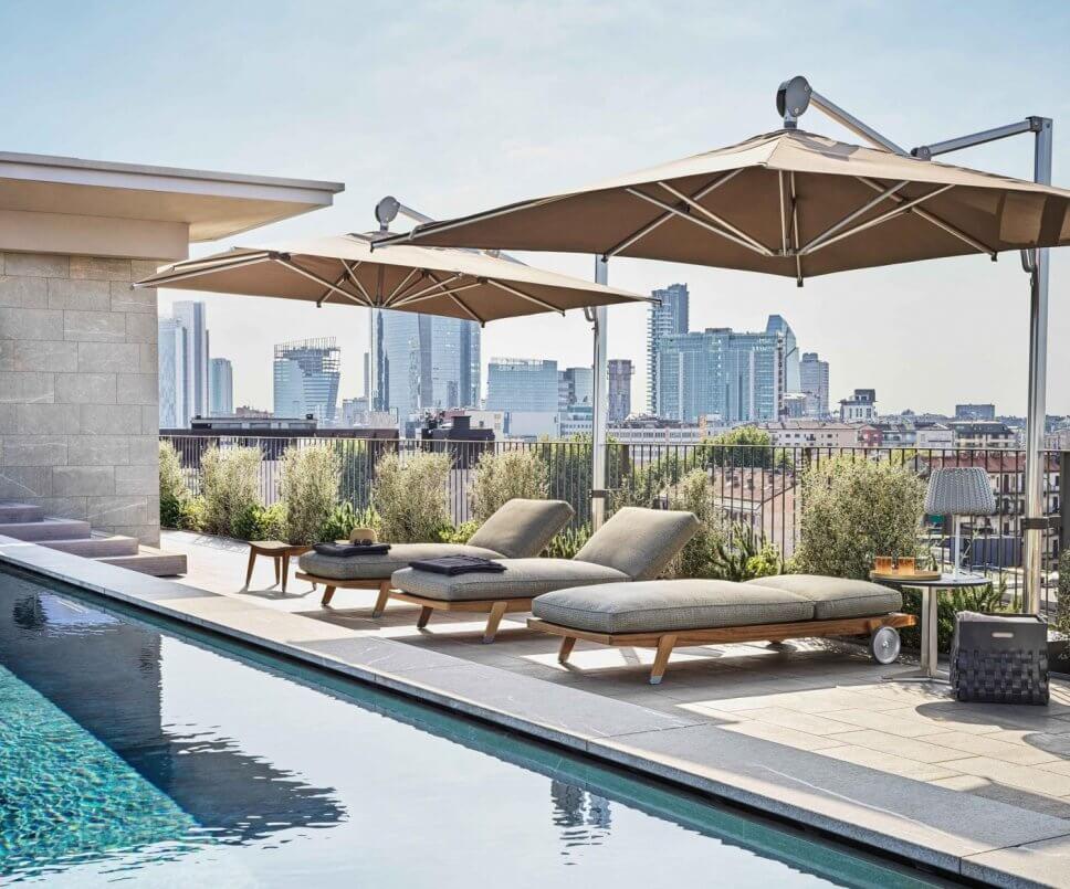 Modernes Sonnenliegen auf Dachterrasse neben Pool