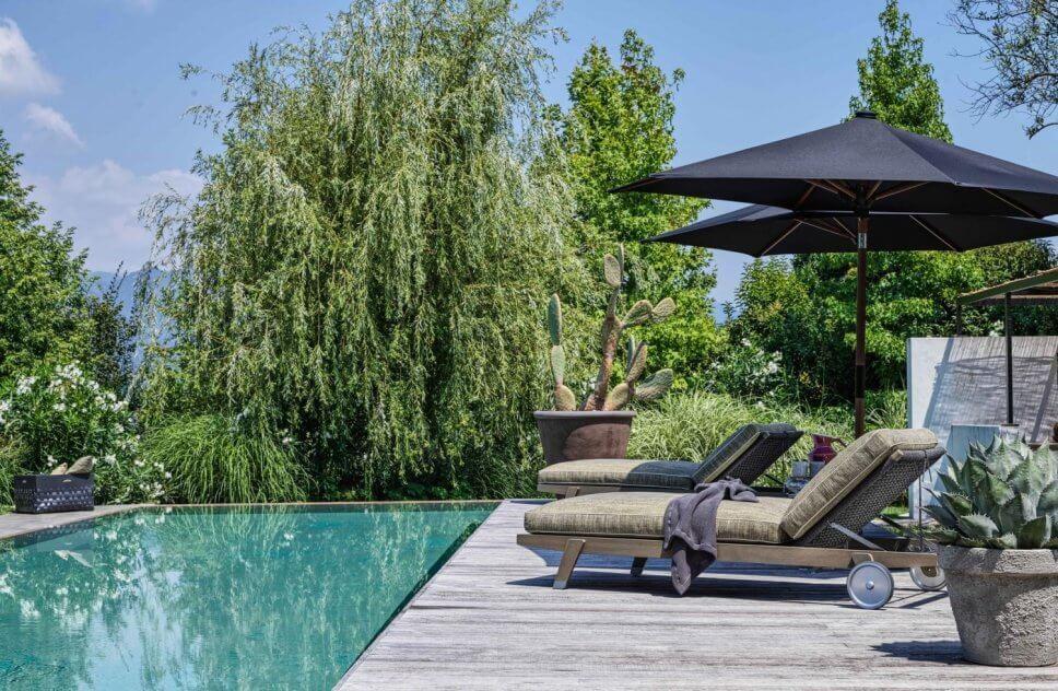 Modernes Sonnenliegen auf Terrasse neben Pool