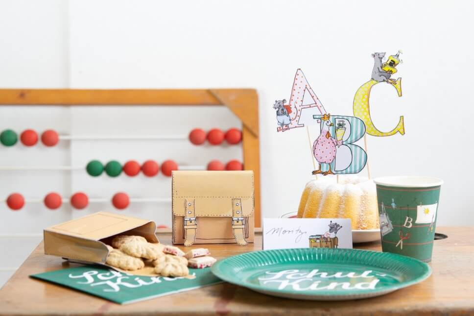 Kuchen, kleine Papierschulranzen mit Keksen gefüllt auf Tisch
