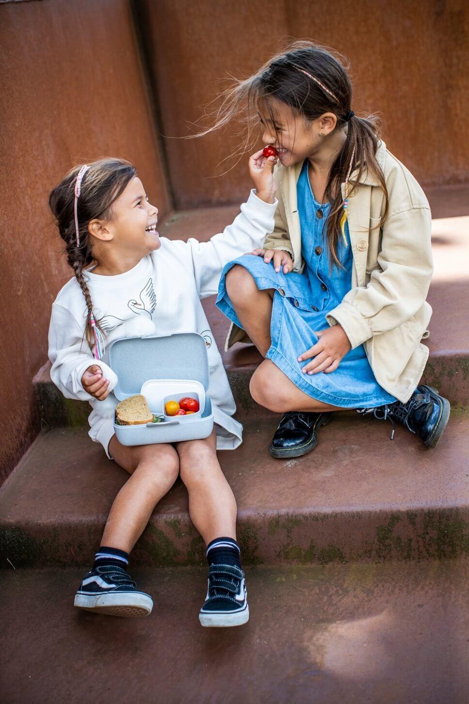 Zwei Mädchen sitzen mit einer Brotdose auf Stufen
