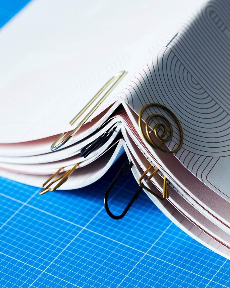 Verschewiden geformtte Büroklammern klemmen an mehreren übereinander gestapelten Heften