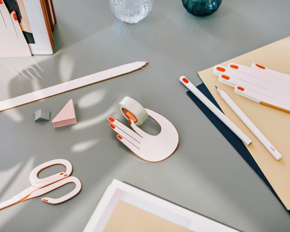 Bunte Notizhefte und Stifte in Hand-Form