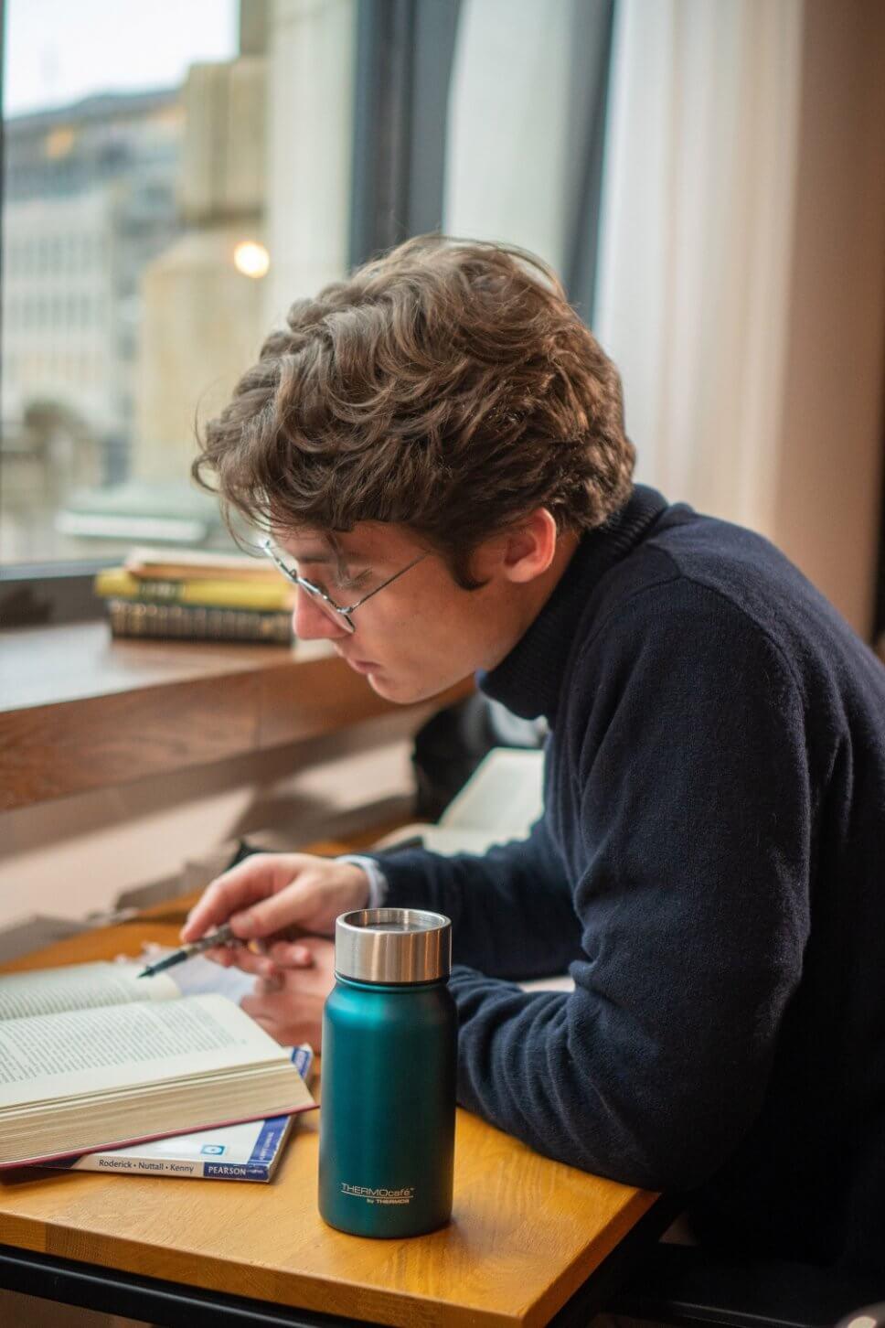 Junger Mann sitzt am Schreibtisch, darauf ein Thermosbecher