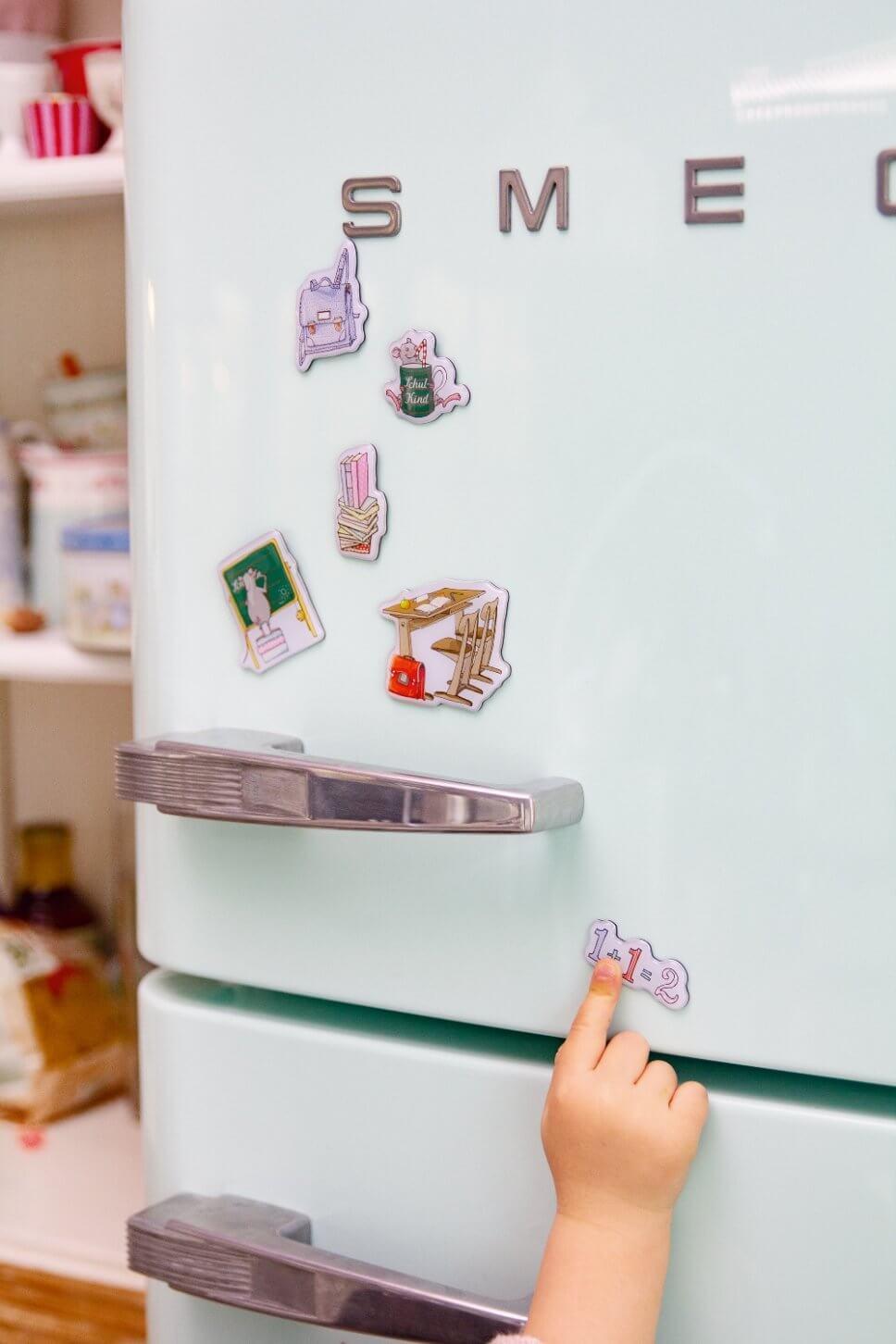 Bunte Magneten mit Schulmotiven am Kühlschrank