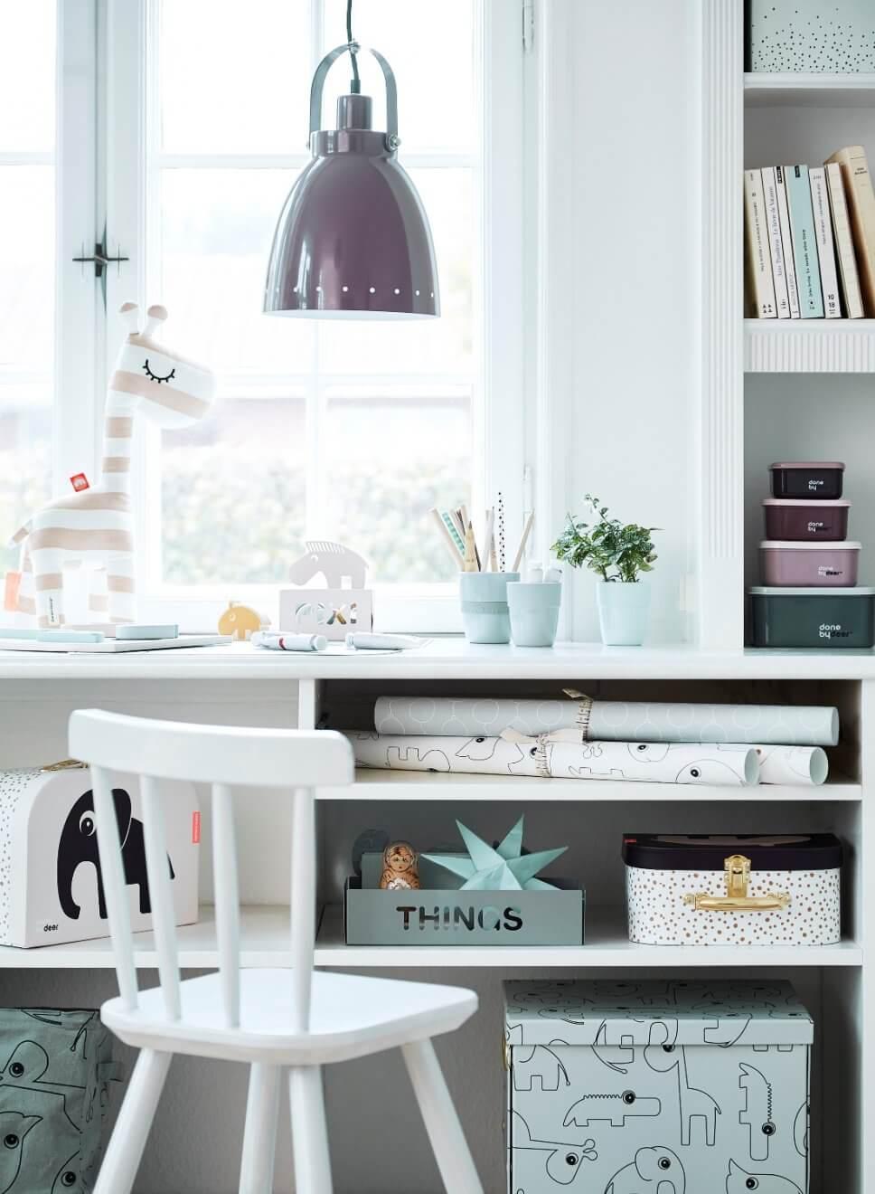Schreibtisch mit Schachteln, Heften und Stiften