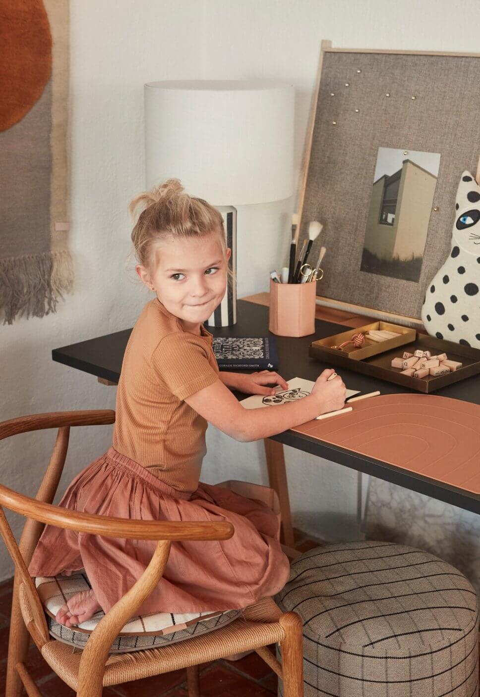 Mädchen sitzt an Schreibtisch mit Heften und Stiften