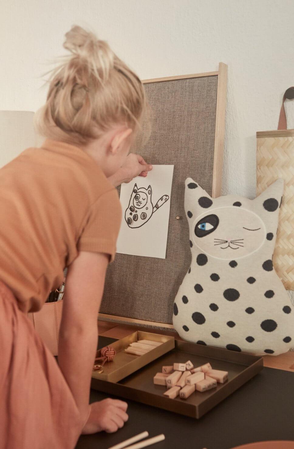 Mädchen pinnt an Schreibtisch ein Bild an eine Pinnwand