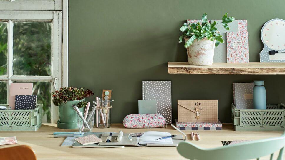 Schreibtisch mit bunten Heften und Stiften