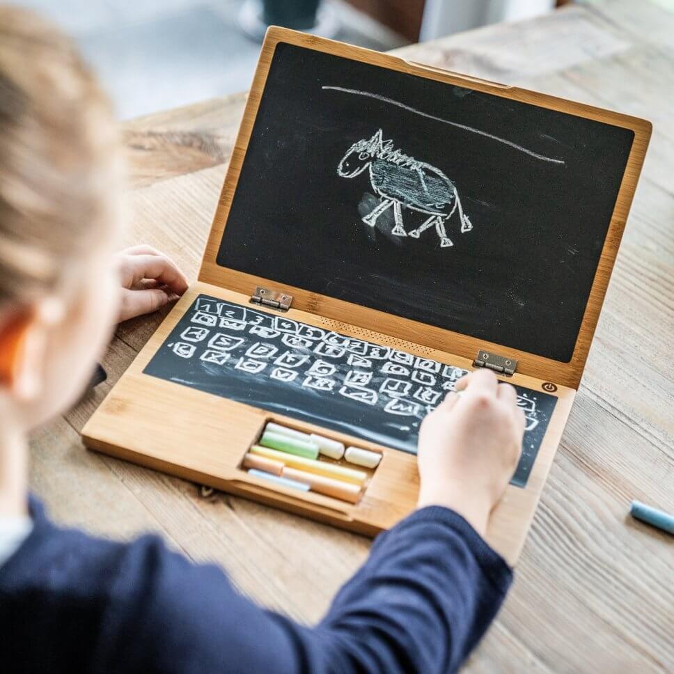 Mädchen bemalt Tafel in Form eines Laptops