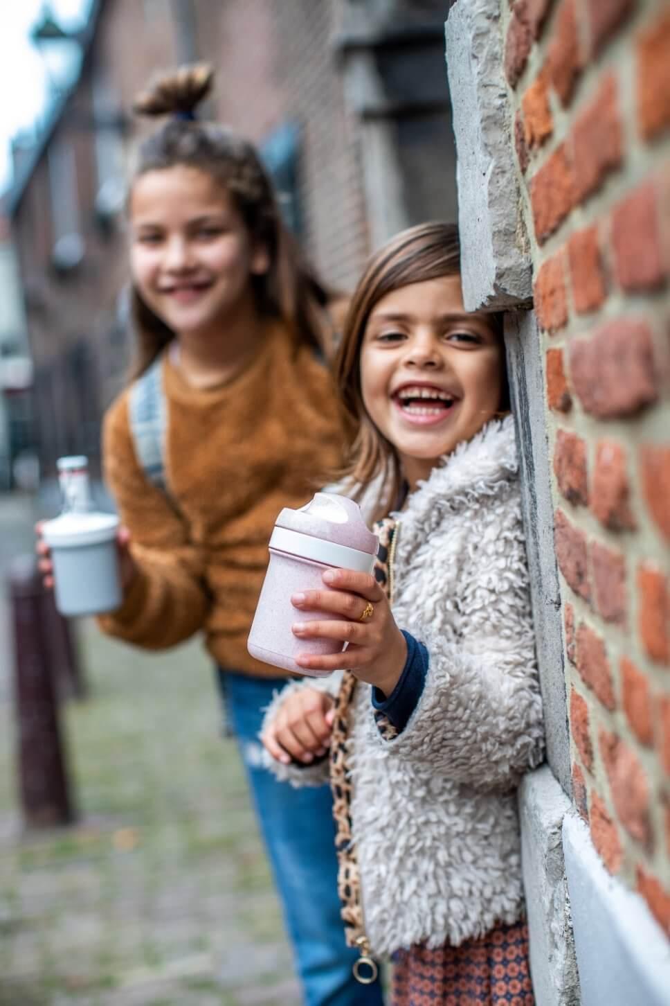 Zwei Mädchen stehen mit Trinklflaschen im Hauseingang