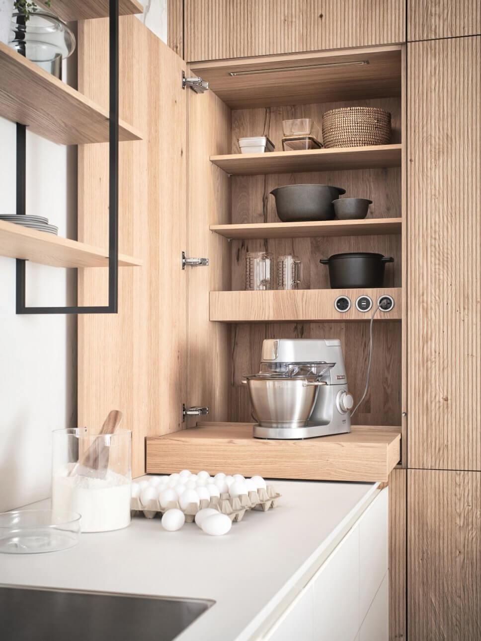 Moderne offene Küche mit Küchenmaschine hinter geöffneter Schranktür