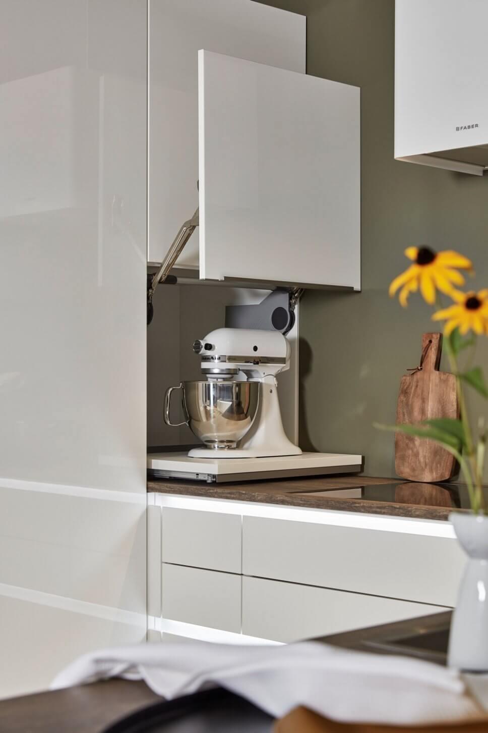 Moderne offene Küche mit Küchenmaschine hinter geöffneter Lifttür