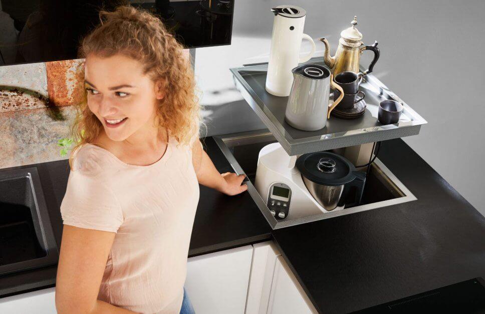 Frau versenkt Küchenmaschine auf Tablar im Küchenschrank