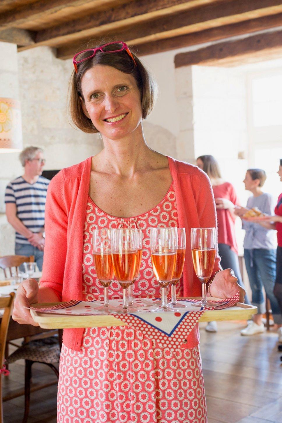 Frau trägt Tablett mit gefüllten Champagnergläsern in altem französischen Landhaus