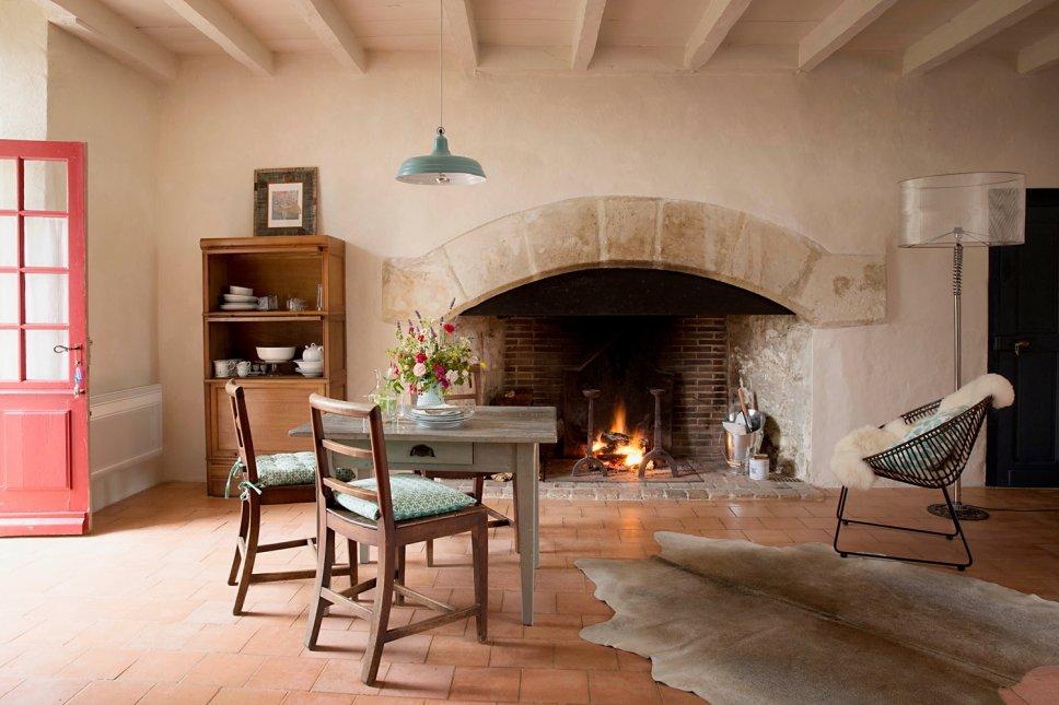 Farbenfroh und nostalgisch eingerichtetes Esszimmer mit großem Kamin in altem französischen Landhaus