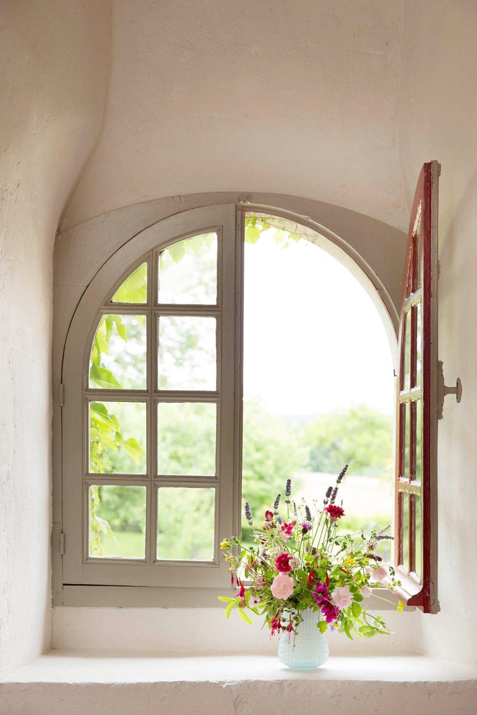 Offen stehendes halbrundes Fenster mit Wiesenblumenstrauß auf der Fensterbank