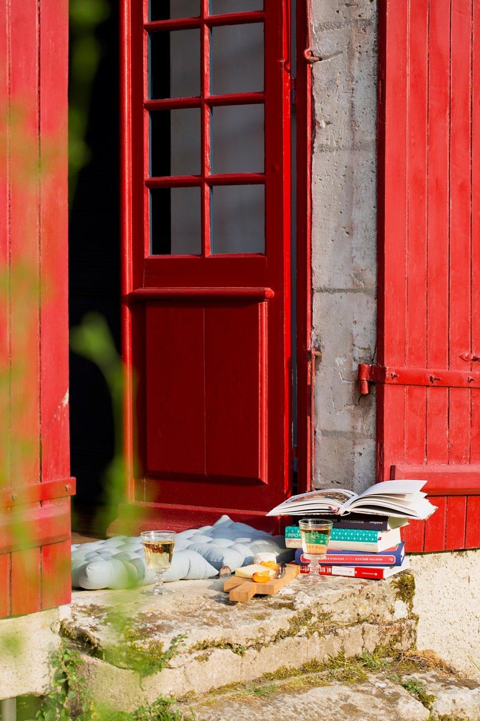 Weingläser, Käsebrett, Bücher und bunte Sitzkissen auf Türschwelle in altem französischen Landhaus