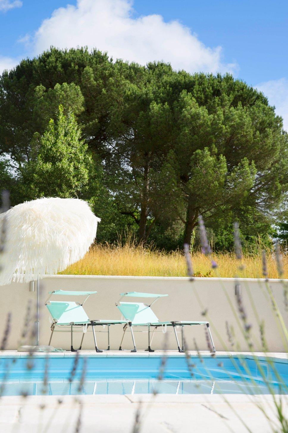 Liegestühle und Schirm vor Swimming Pool