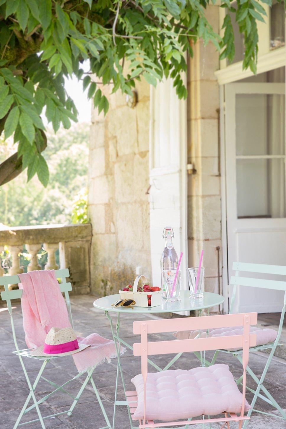Farbenfroher Bistrotisch und Stühle auf Terrasse in altem französischen Landhaus